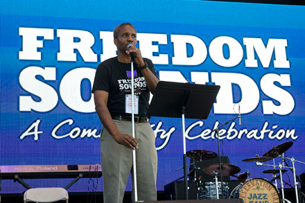 Program co-curator Mark Puryear announces the next act on the Freedom Sounds Stage.