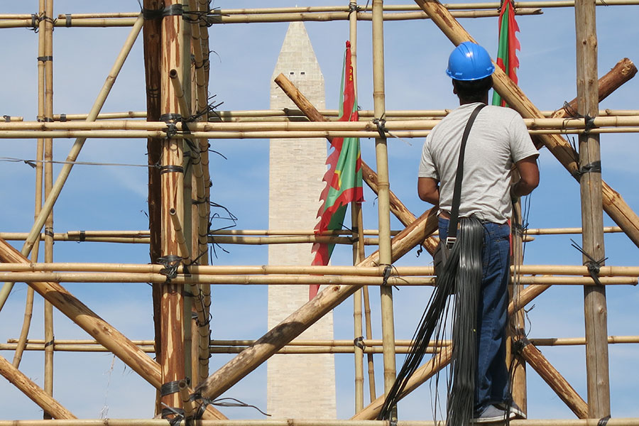 Sit Kar Lok, the most experienced craftsman on the team, takes a break while taking in the view of the Washington Monument during the third day of installation.