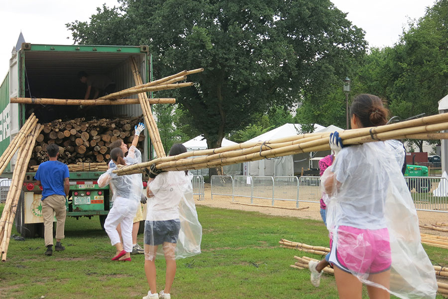 On a rainy day, China program team members Jing Li, Joan Hua, and Danielle Wu assist in loading the materials into a shipping container.