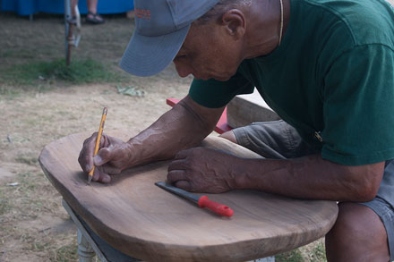 Earl Kawa'a adds his signature—a Hawaiian voyaging canoe—to the poi pounding board.