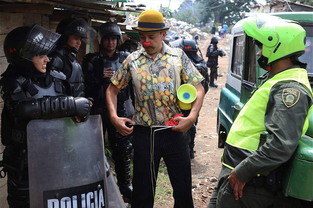 A Clowns Without Borders artist performs for riot police preparing to raze a settlement in Colombia.