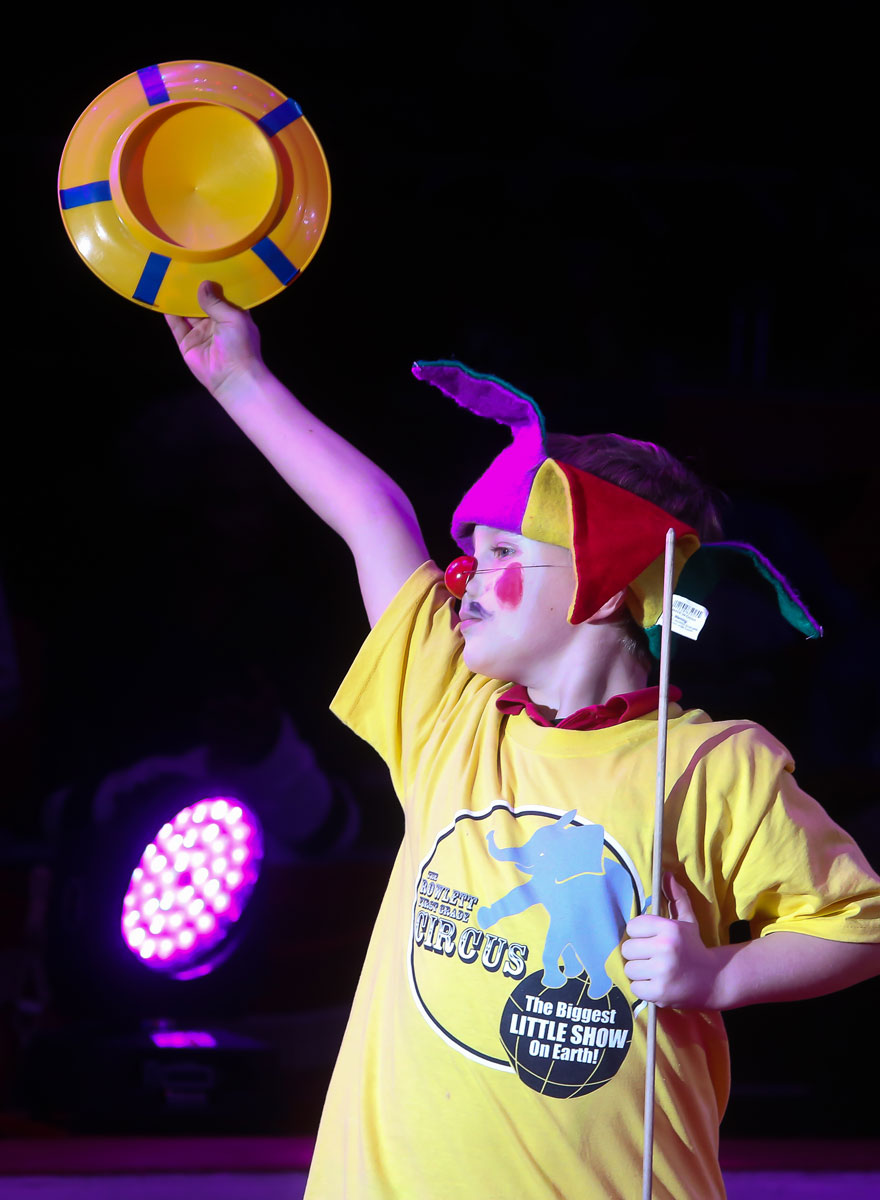 A first grader triumphantly holds up his plate after successfully spinning it in the Circus Sarasota Big Top with Build-a-Circus.