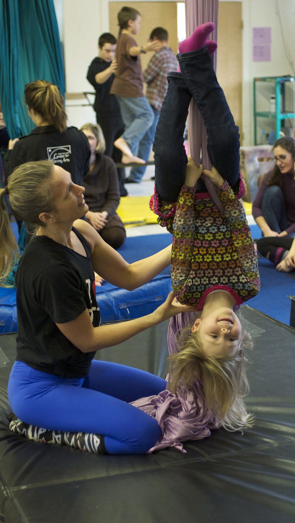 Youth program director Erin Lovett Sherman assists a young artist on the silks.