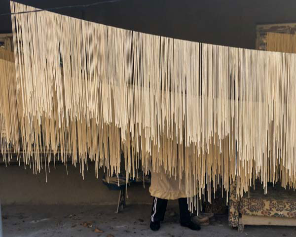 Women prepare arishta, a hand-pulled pasta, and hang the long noodles on a line to dry.