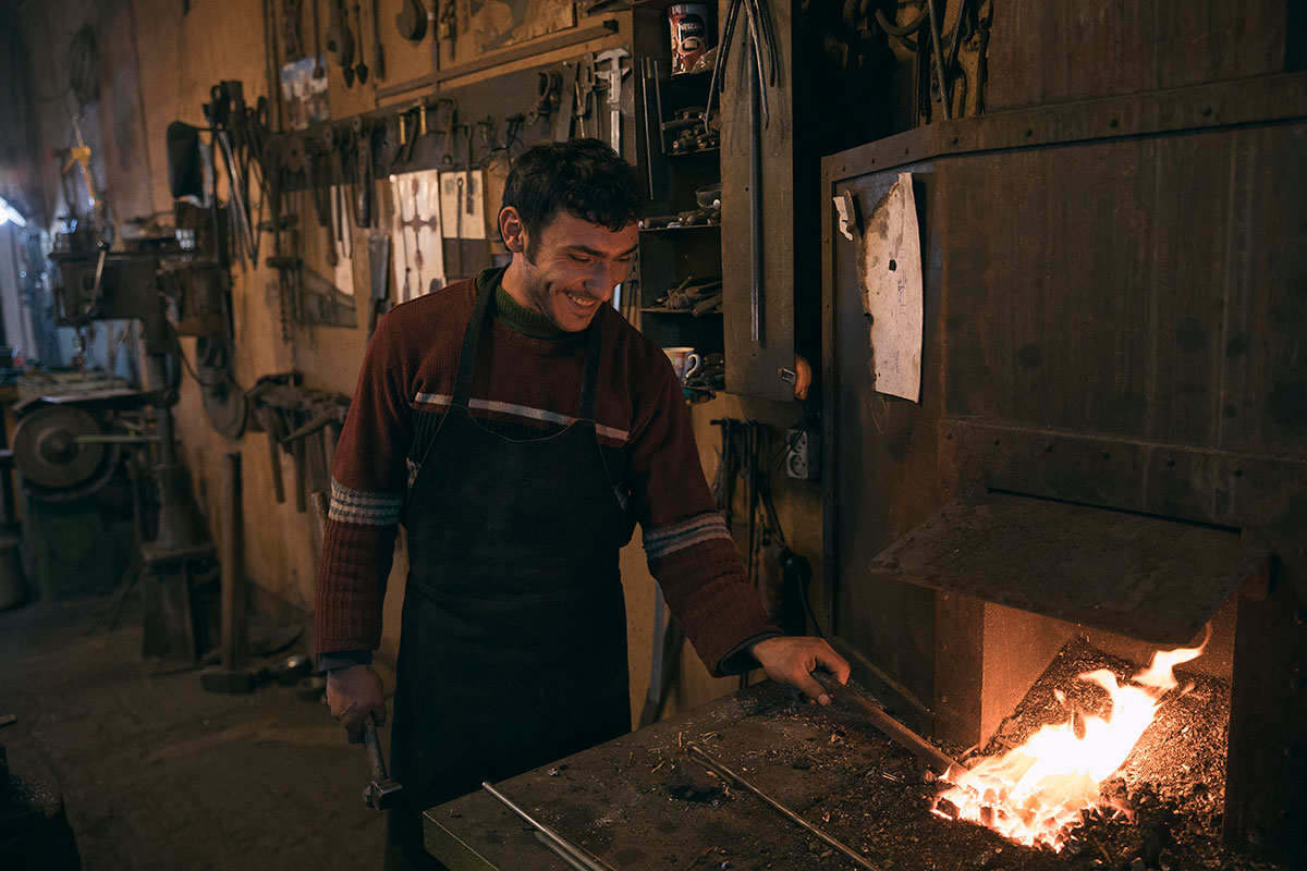 Blacksmith Hovhannes Mnoyan heats a piece of iron in the forge.