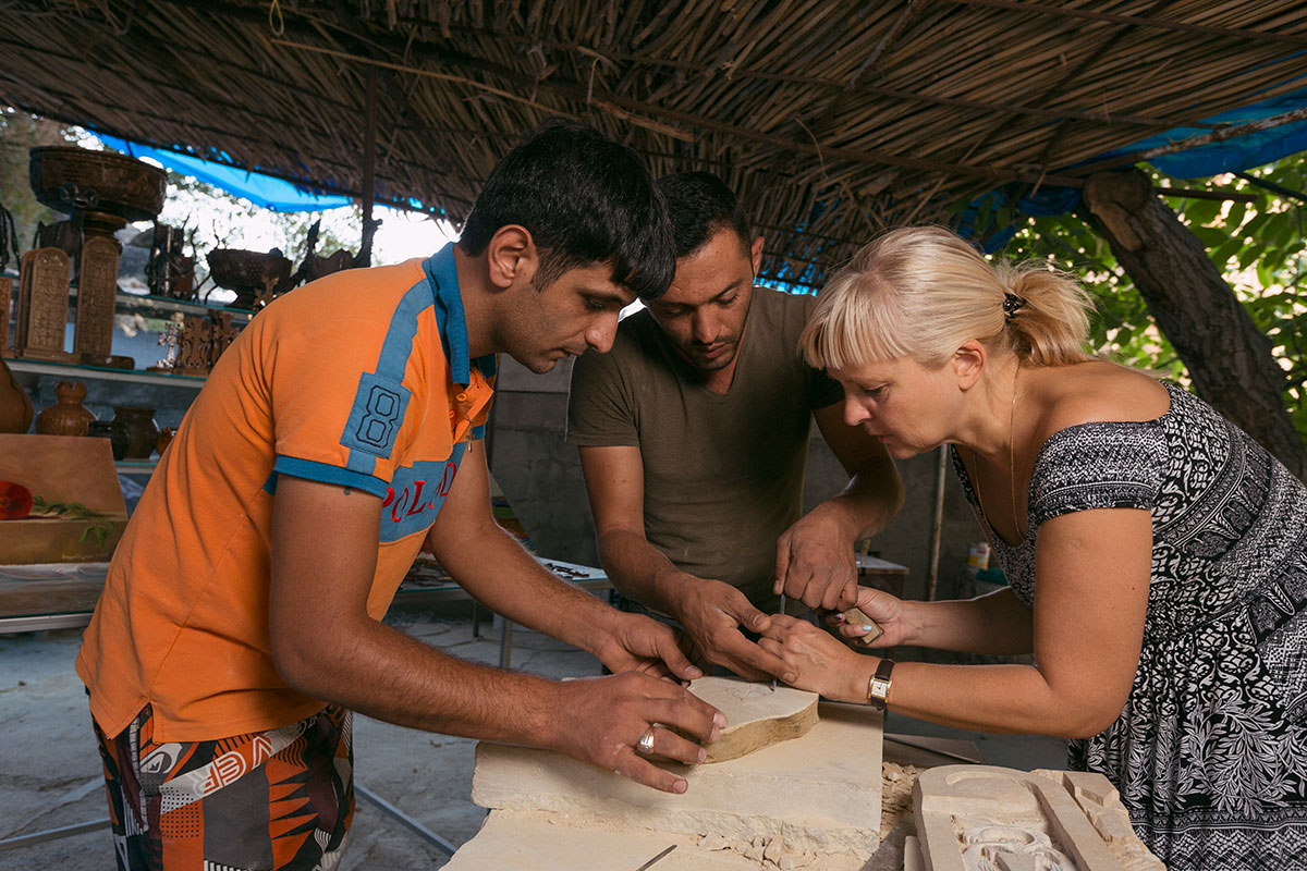 The Ghazaryans demonstrate carving for tourists on their way to visit Noravank monastery. Some of the most curious tourists also try their hand at carving.