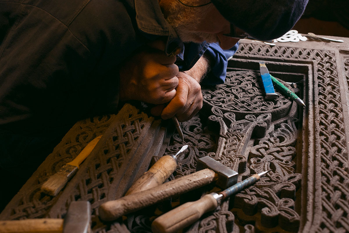 Hovhannisyan works on the detail of a khachkar made of black tuff stone.