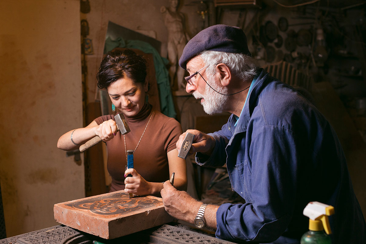 Hovhannisyan supervises as apprentice Gayane Manucharyan carves a piece of red tuff stone.