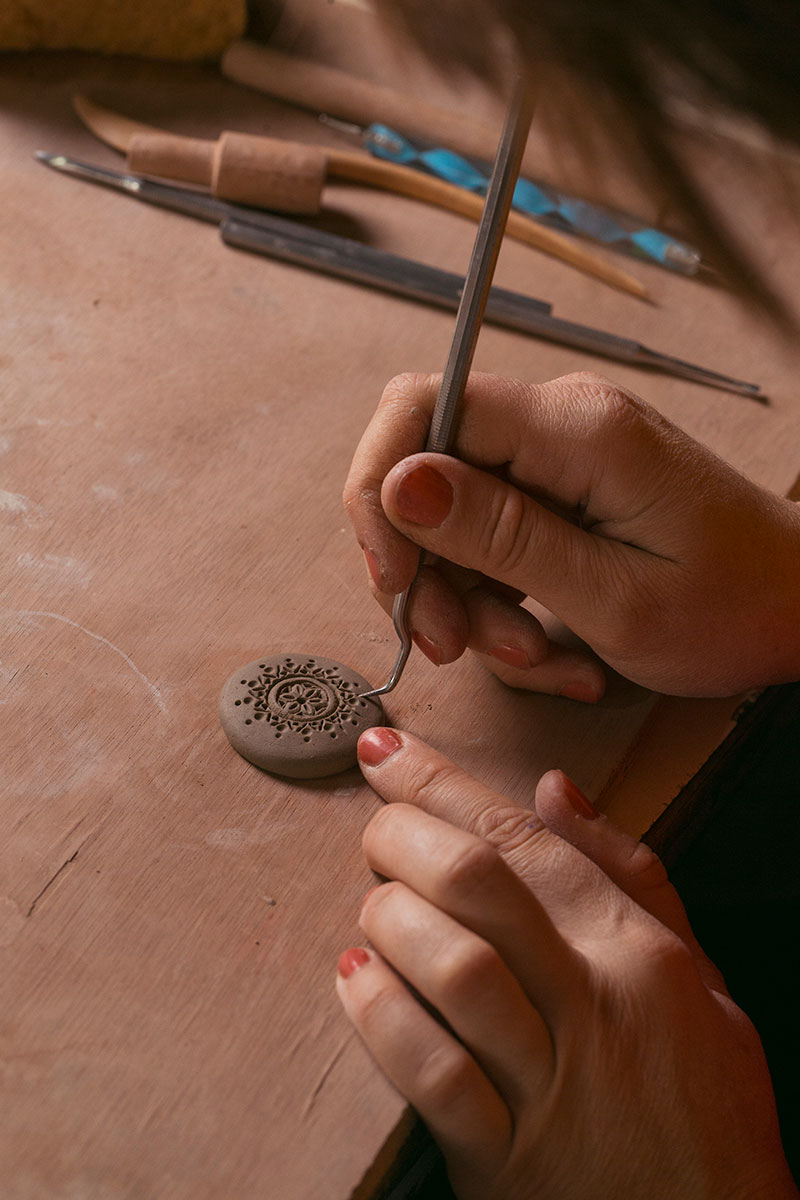 Gasparyan adds detail to a clay pendant.