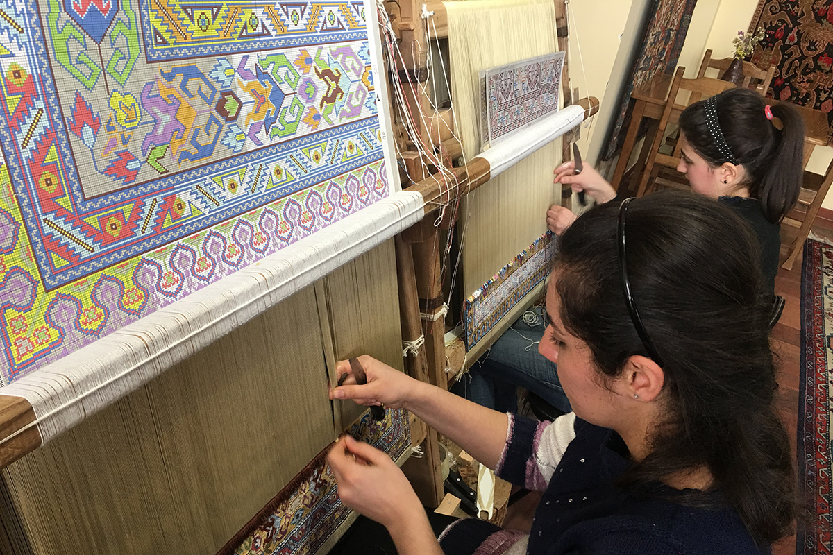 Students work on silk carpet designs at Silk Road Hotel in Yerevan.