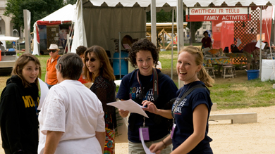 Interns Kathryn Young (right) and Sara Manco (center) chat before the Welsh hymn singing at the 2009 Smithsonian Folklife Festival.