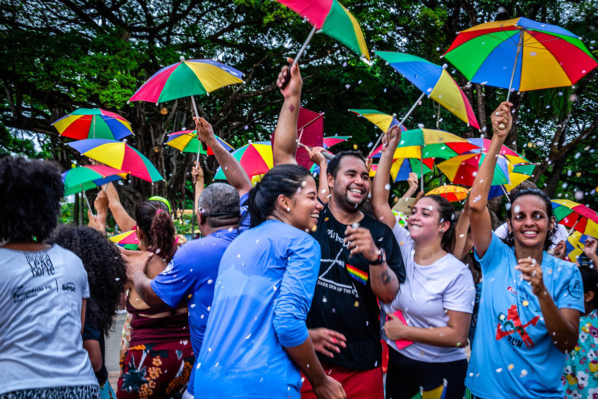 A group of young people dance outside, looking ecstatic, holding up small rainbow-colored umbrellas as confetti rains down.