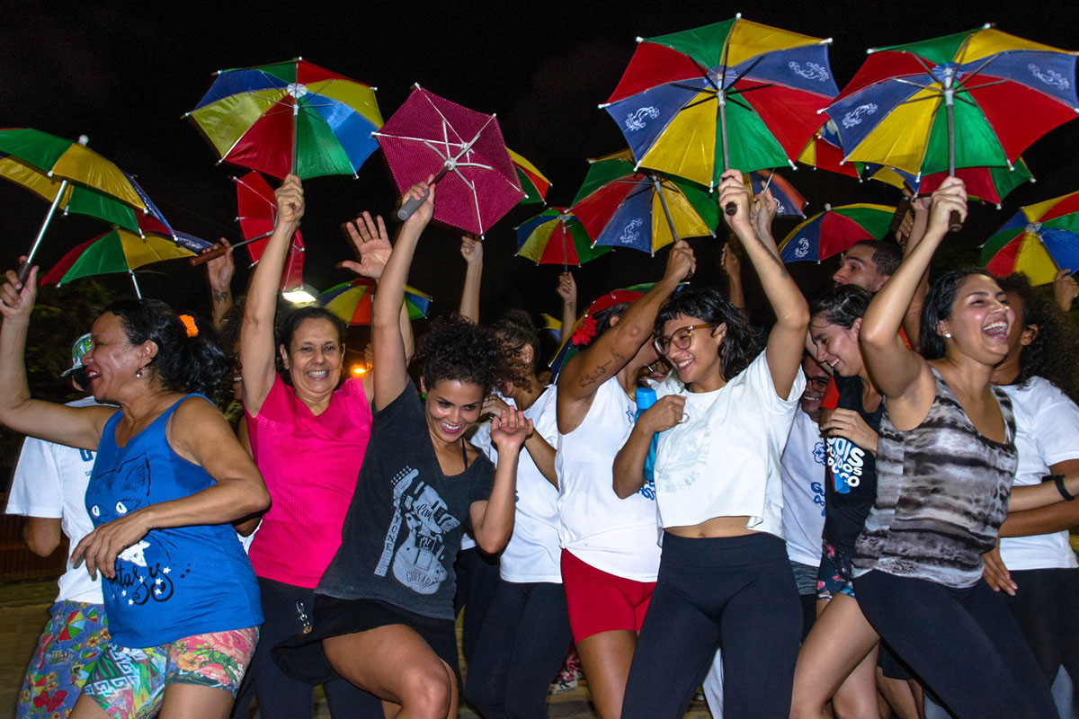 People dancing outside, looking joyous and raising up small rainbow-colored umbrellas. The sky is dark, but they are lit up.