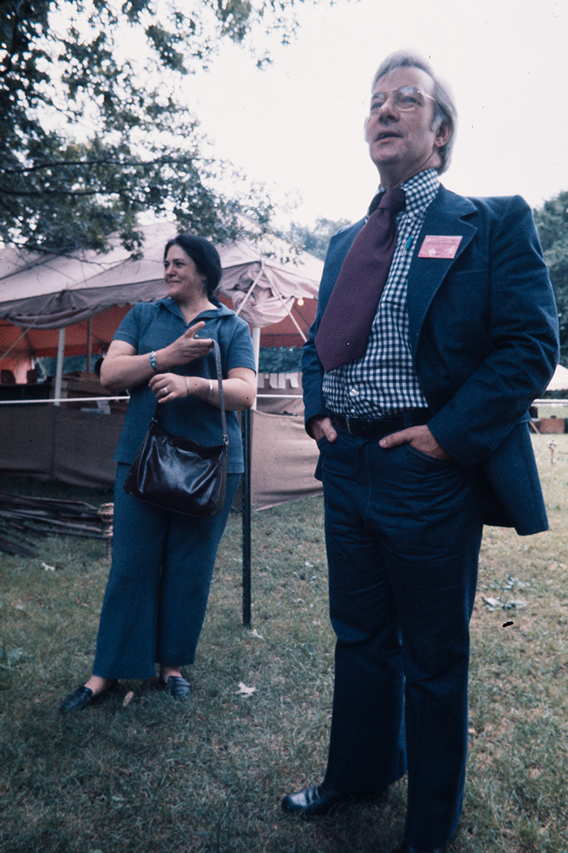 In the foreground, a man standings with his hands in his pockets, wearing a navy suite with a wide burgundy tie. Just behind him in a woman looking in the same direction. Behind them, an empty Festival tent.
