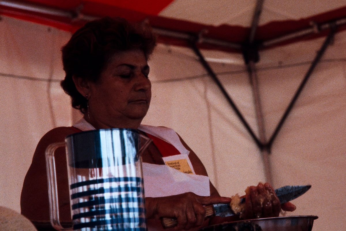Inside a white and red tent, a woman slices something in her hand with a kitchen knife.
