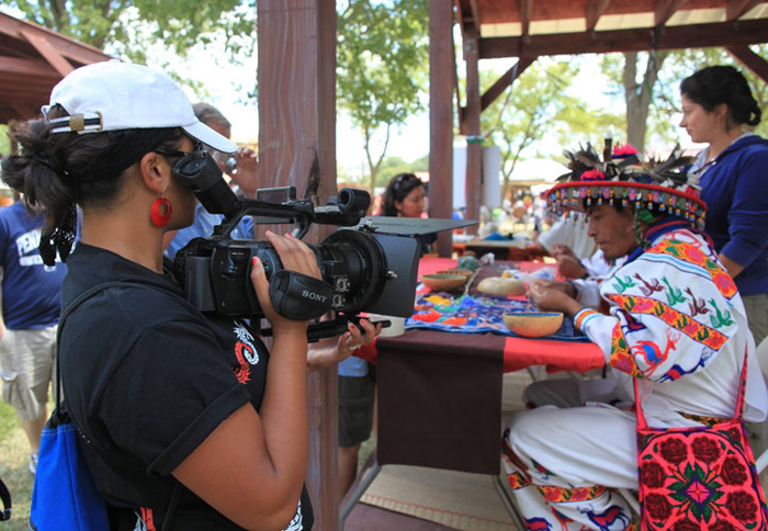 In the foreground, a volunteer with their face covered by a large video camera and white hat film an artisan dressed in bright white and neon pink traditional outfit.