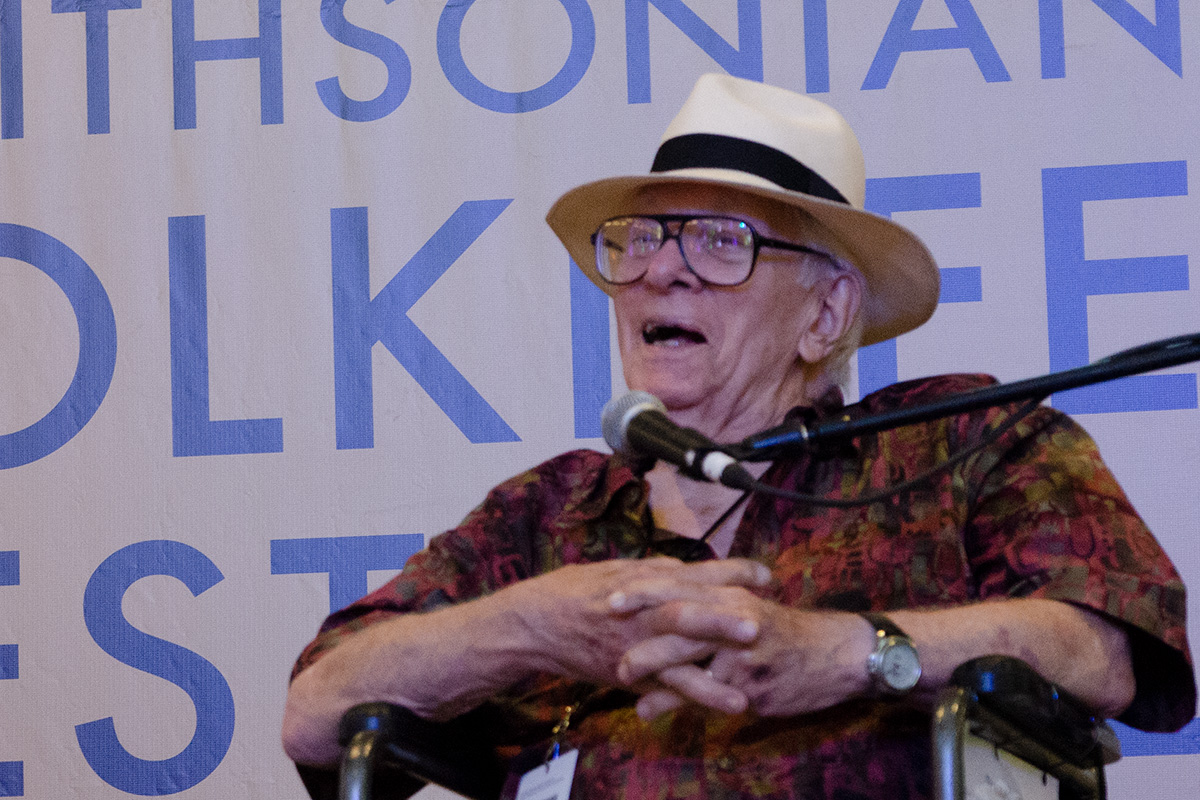 A much older Jim Morris sits on a Smithsonian Folklife Festival stage, speaking into a microphone. He wears glasses, a tan fedora, and a short-sleeved dress shirt.