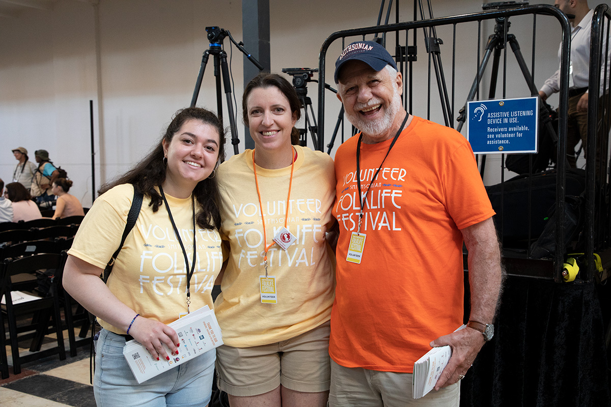 Three volunteers, two in yellow and one in orange Festival Volunteer T-shirts, pose in front of a sound booth. All smiling.