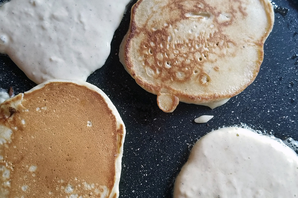 Pancakes cooked in a black fry: two golden brown on top, two still cooked and pale