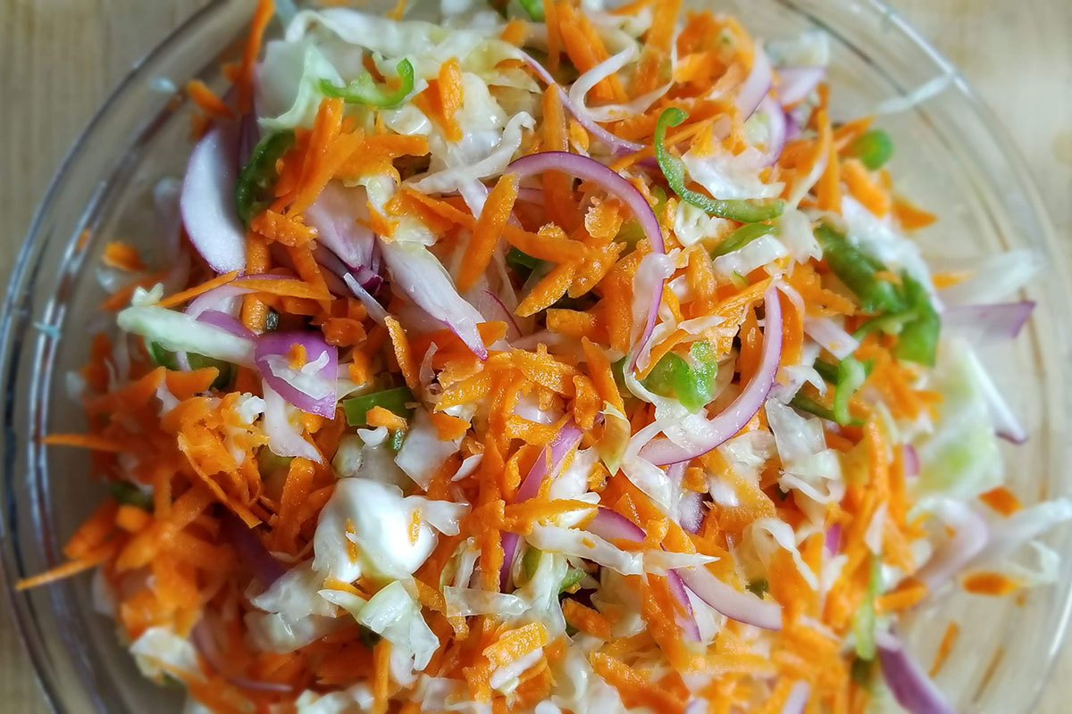 Shredded green cabbage, orange carrots, purple onions, and green pepper ready for pickling.