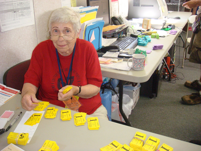 Volunteer sits behind a table in one of the Festival trailer offices, counting yellow meal tickets, priced $1 and $5. She wears a red Folklife Festival T-shirt.