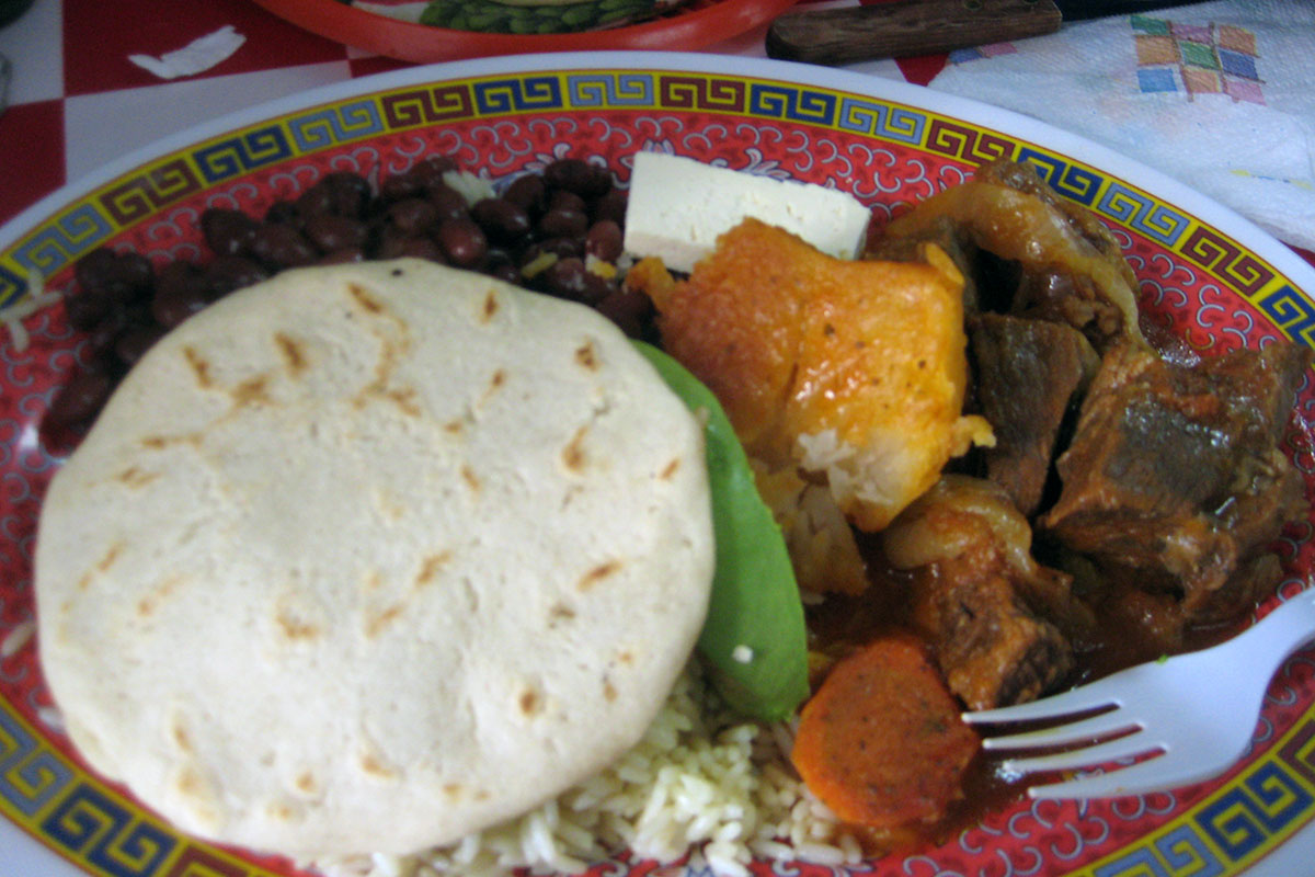 Rice, vegetables, meat, and a pupusa on a plate with a Chinese pattern around the rim and a plastic fork sticking out.