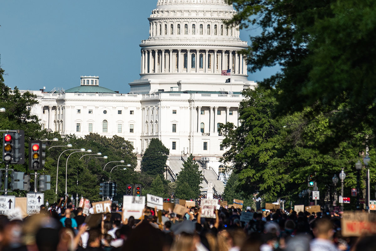 View of the west side of the U.S. Capitol Building, with a crowd of protestors heading toward it in the foreground.