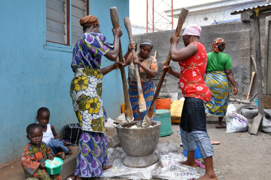 Women work together to pound boiled yam