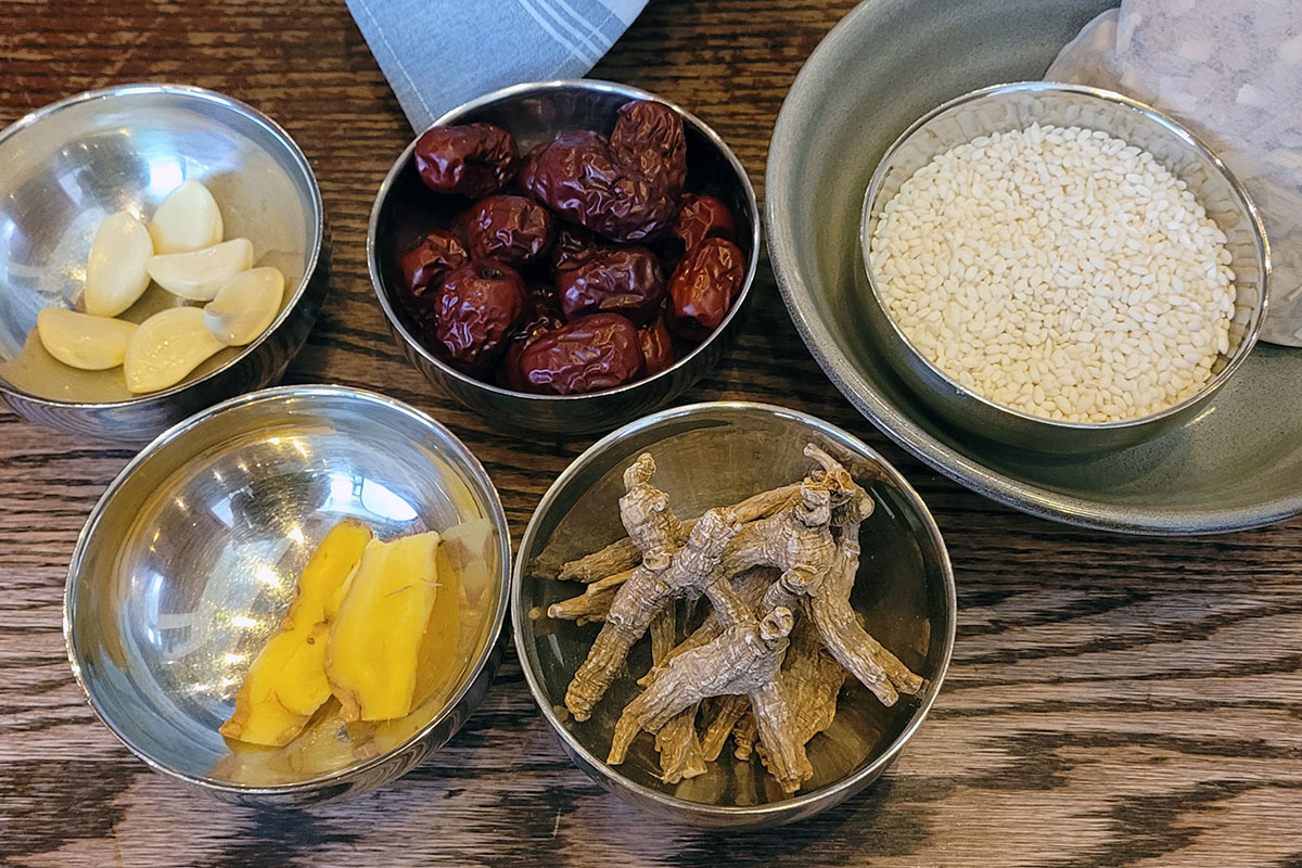 Five metal bowls with food ingredients: peeled garlic cloves, dried red fruit, rice, brown ginseng roots and a strip of yellow ginger root.