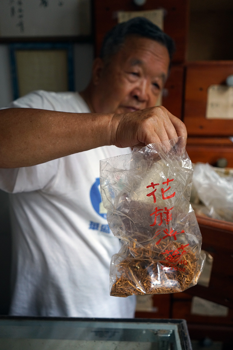 Dr. Shi-hua Wu holds up a clear plastic bag of dried American ginseng
