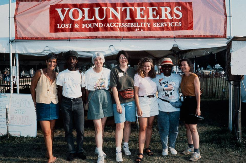 Vintage film photo of seven volunteers, arms around each other, posing in front of the tent marked: VOLUNTEERS / LOST & FOUND / ACCESSIBILITY SERVICES