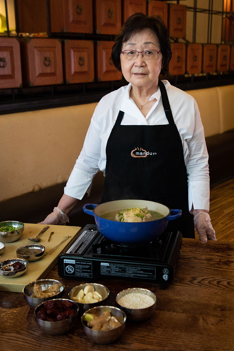 A woman in a black apron stands at the cooking station, a soup bowl on a burner and prepared ingredients in a small metal bowl.