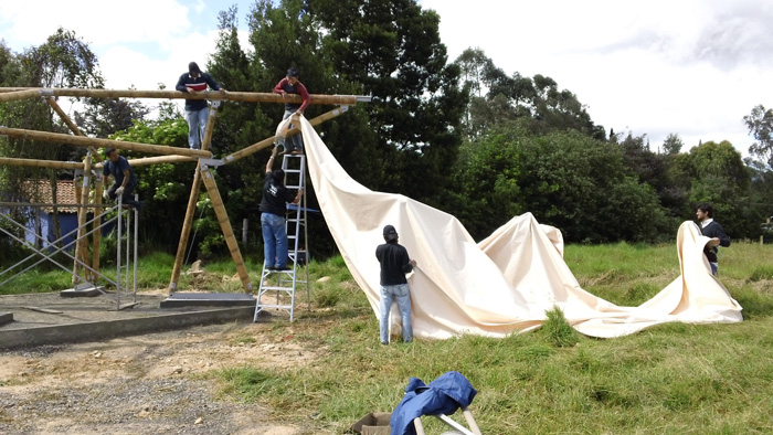 Pulling white canvas over bamboo frame, photo by and courtesy of Francisco Quiñónez