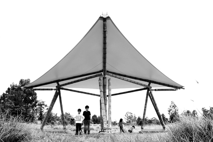 Children under finished guadua tent.