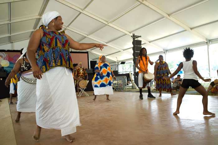 A young audience member jumps onto the dance floor during a performance by the African Heritage Dancers in the Panorama Room stage of the Citified program. Photo by Carsten Schmidt, Smithsonian Institution
