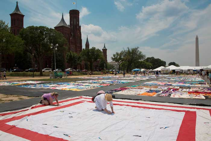 "Visitors leave their names and messages on a ""signature square,"" which is typically displayed with The AIDS Memorial Quilt.  Photo by Francisco Guerra, Smithsonian Institution"