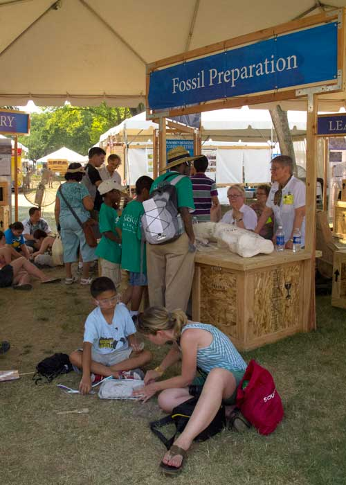Visitors learn about paleontology in the Montana State University tent.