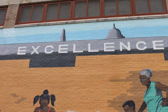 A mural decorating the Benning Park Community Center expresses the importance of excellence to the neighborhood.