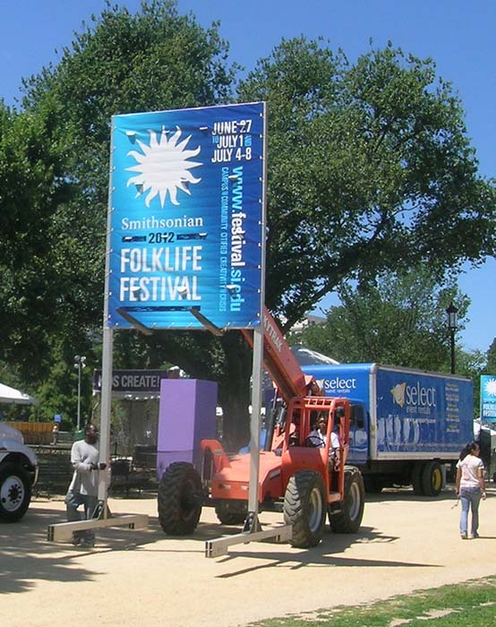 Technical staff do some heavy lifting to relocate a Festival sign.