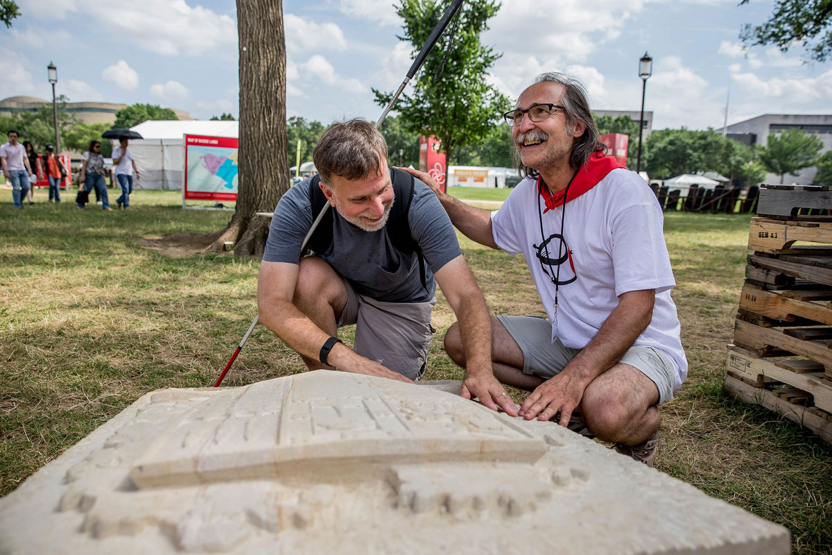 Basque stone carver Bernat Vidal guides a visitor at the 2016 Festival. Photo by Prayoon Charoennun