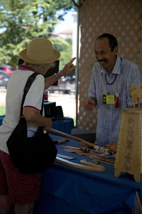 Alexander Nikolaevich Nasakaev, a Kalmyk instrument maker and woodcarver, talks with a participant in the <i>One World, Many Voices</i> program. Photo by Jennifer Graham, Ralph Rinzler Folklife Archives