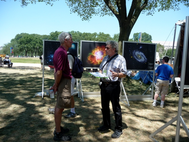 Center for Folklife and Cultural Heritage curator Jim Deutsch (right) confers with Chris Eagan from the Smithsonian Astrophysical Observatory. In the background are part of the eye-catching display depicting views from space.