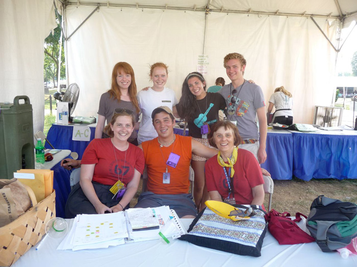 Betty Belanus and her interns convene at the Volunteer Tent for an afternoon meeting. Standing, left to right: Interns Hester Clarke, Casey Carlson and Lauren Lauzon, and Accessibility Aide Brendon Ziebarth; seated, left to right: Interns Meghan Burke and Jeremy Krones, and Curator Betty Belanus