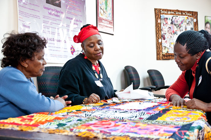 Workshop participants admire a quilt-in-process made of fabric from Nigeria.