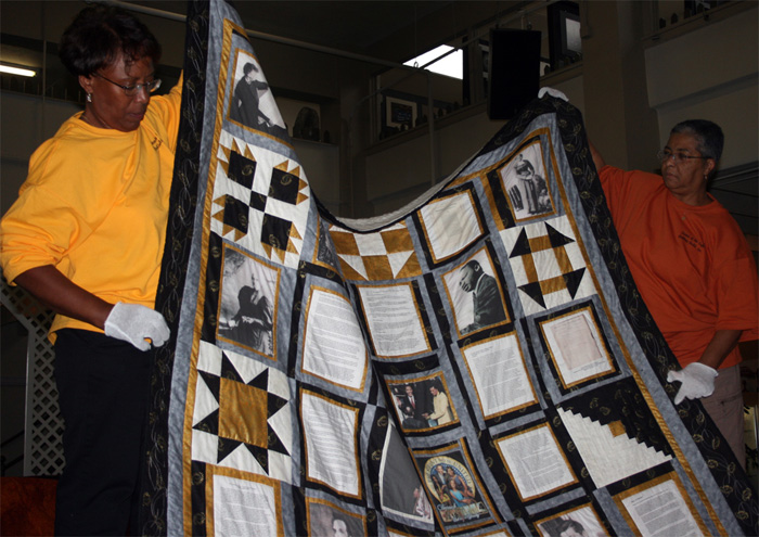 Maxine Stovall and Kathy Muhammad holding an African American history themed quilt made by a member of the Sisters of the Cloth Quilting Guild in Fort Wayne, Indiana. Photo by Jon Kay