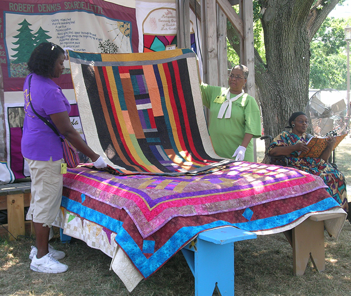 Sisters of the Cloth, affiliated with Indiana University's Traditional Arts Indiana program, demonstrate Bed Turning at the Commons.
