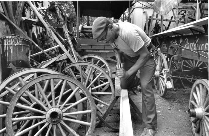 "Walter ""Teeth"" Kelly mending wagons at the Kratz stable. Teeth was a master wagonmaker and made or fixed most of the Arabbers' wagons. Southwest Baltimore, Maryland, July 1986. Photo © 2012 Roland L. Freeman"