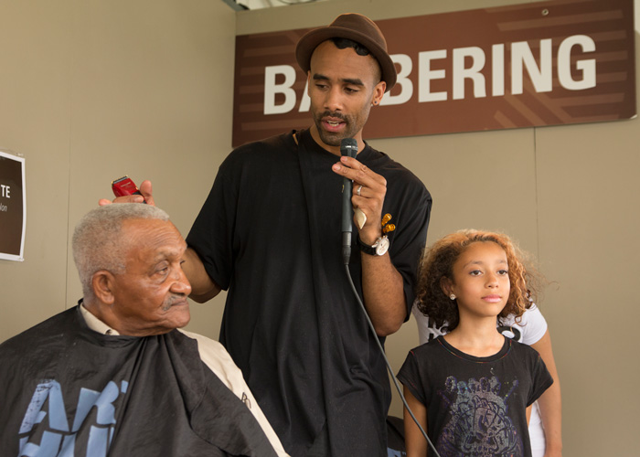 Dusan Grante, creative director of Arthur Christine Salon, describes the cut he is giving to Mr. Diggs, a Baltimore Arabber whose family has been participating in the Smithsonian Folklife Festival for since 1967. Photo by Pruitt Allen, Ralph Rinzler Folklife Archives