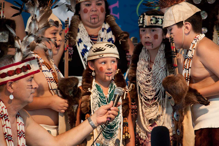 Siletz cultural expert and language educator Bud Lane holds the microphone as young members of the Confederated Tribes of Siletz Indians sing a traditional chant at the 2013 Folklife Festival. Photo by Katherine Moore, Ralph Rinzler Folklife Archives