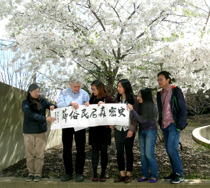 "ing's father wrote this calligraphy, reading ""Smithsonian Folklife Festival"" in Mandarin, displayed by the China program team: curators Sojin Kim and Jim Deutsch, coordinator Jing Li, assistant Joan Hua, and interns Cindy Xu and Mu Qian. Photo by Elisa Hough"